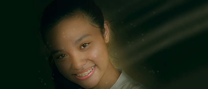 Young girl smiling with an orthodontic appliance