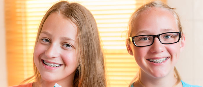two young girls smiling with braces