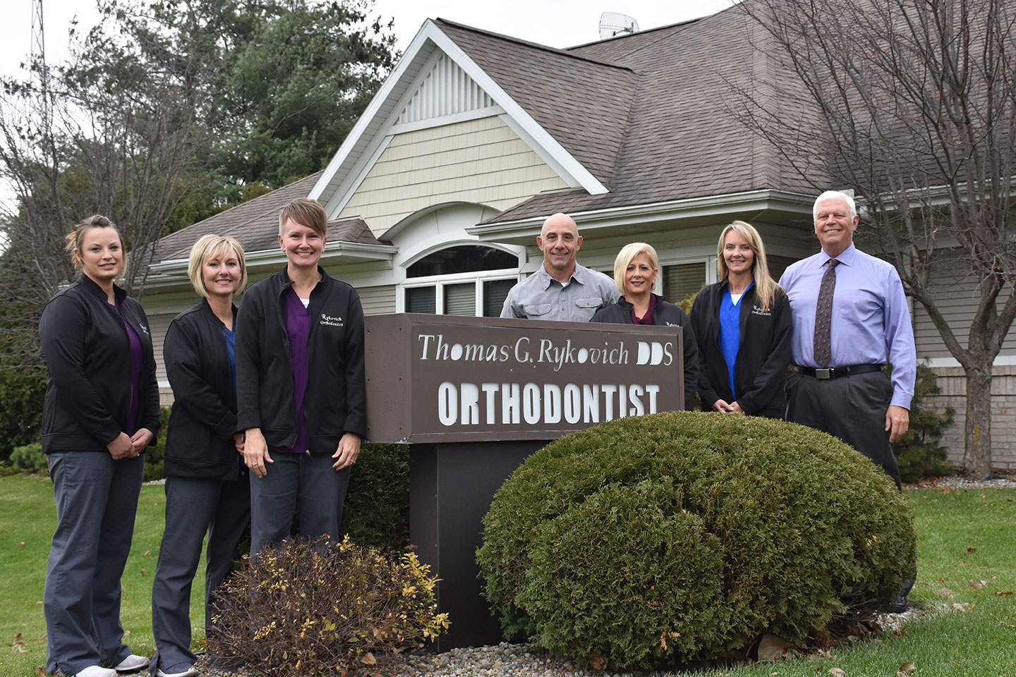 Our dental team standing by our practice sign