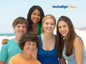 group of teens smiling at the beach with Invisalign Teen logo