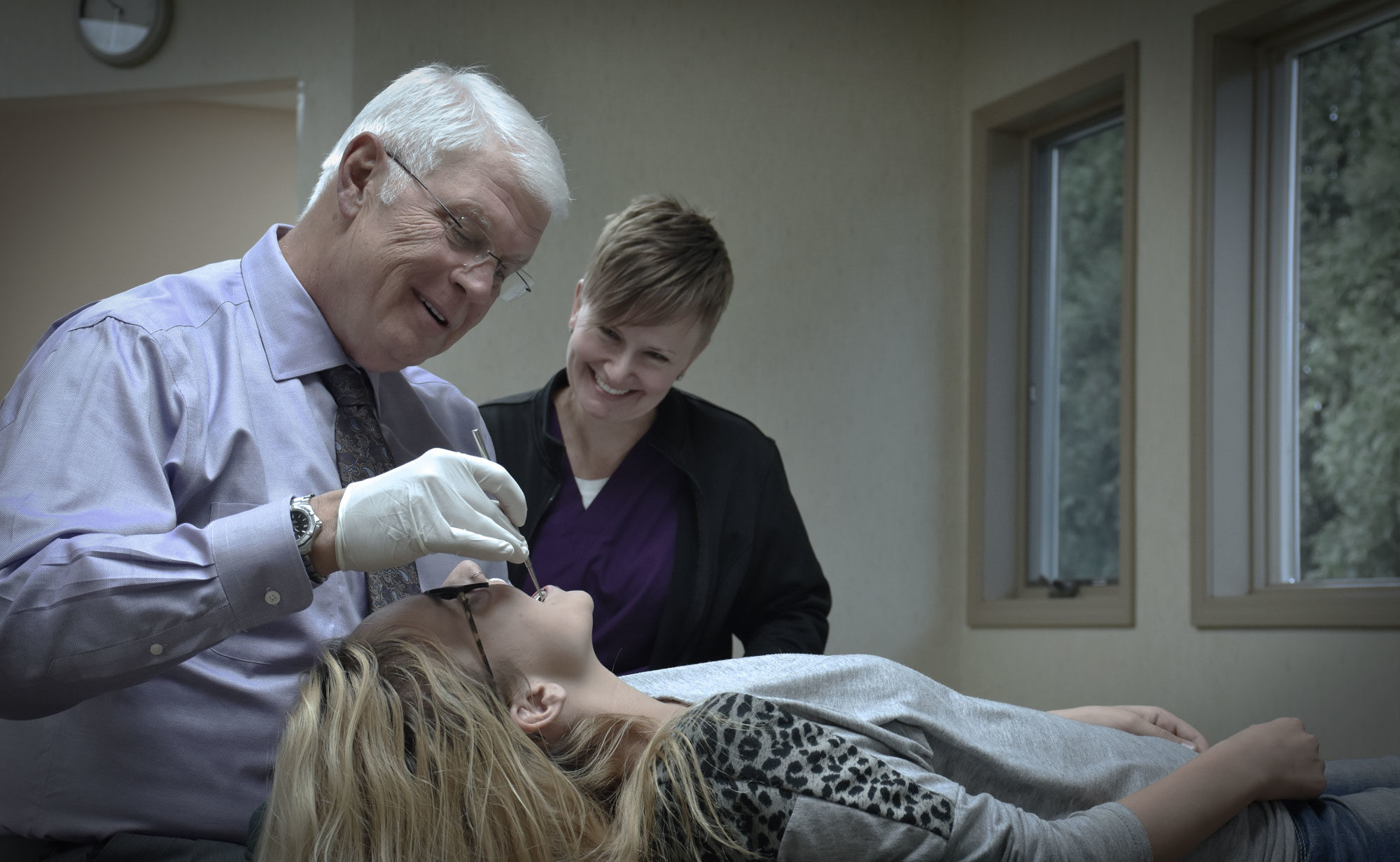 Dr. Rykovich and a female assistant examining a female patient's teeth